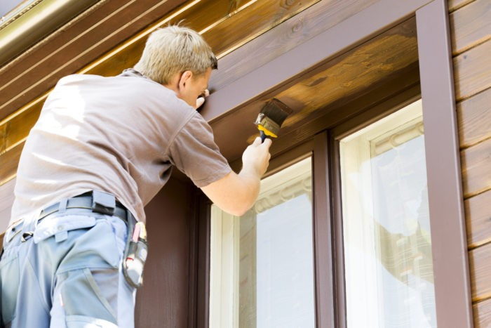 man with paintbrush painting wooden house exterior-We offer professional popcorn removal services, residential & commercial popcorn ceiling removal, Knockdown Texture, Orange Peel Ceilings, Smooth Ceiling Finish, and Drywall Repair